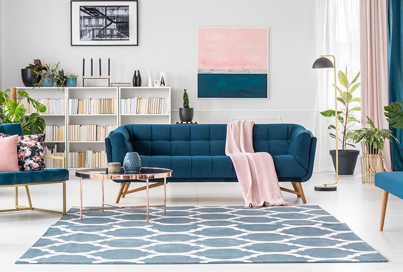 Sala com mesinha de centro, tapete e sofá, além de uma estante de livros e quadros ao fundo